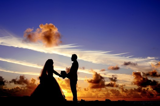 silhouette-of-bride-and-groom-holding-hands-at-sunset
