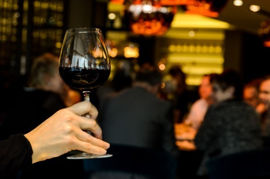 human-hand-holding-wineglass-with-red-wine-in-restaurant